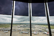 Aerial view (through control tower windows) showing expanse of airport land with airliners at London Heathrow.