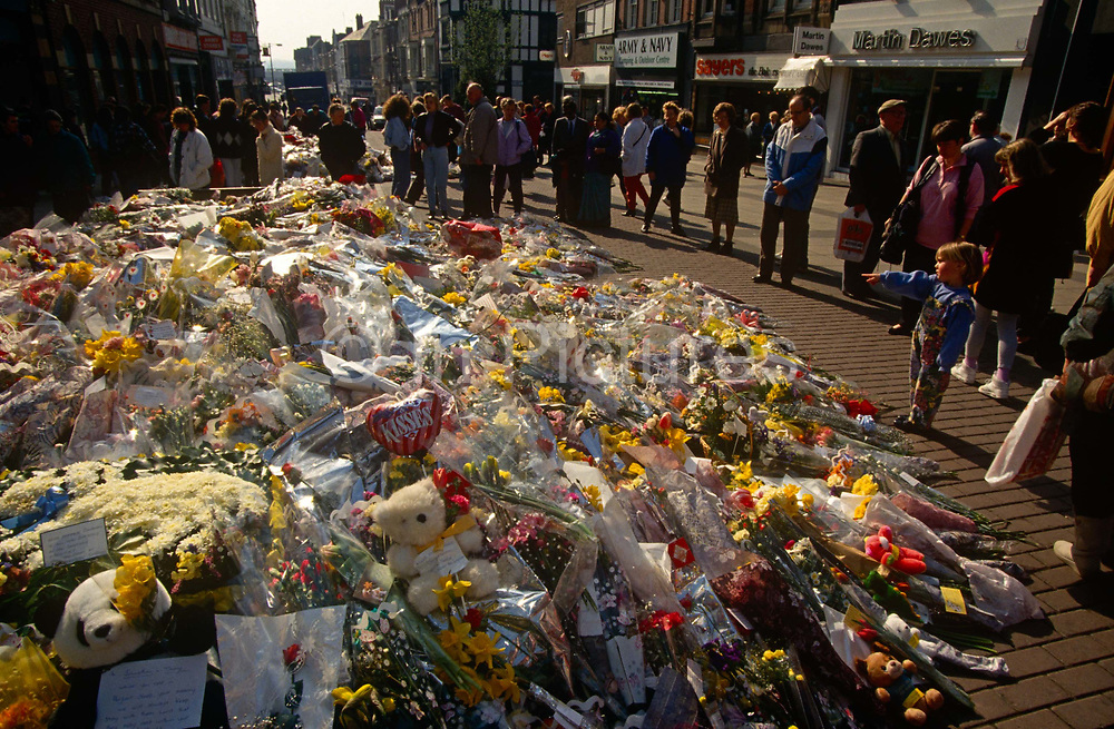 Locals gather to pay their respects to a growing mound of a floral memorial in memory of two people killed by an IRA bomb in the centre of Warrington, Cheshire, England. On 20 March 1993 the explosion by Irish republican terrorists in Bridge Street in the town centre precinct. Two small bombs exploded in litter bins outside a Boots store and a McDonald's restaurant, killing two children and injuring many other people. Although a warning or warnings had been sent, the area was not evacuated in time. Both attacks were perpetrated by the Provisional Irish Republican Army (IRA). Three-year-old Johnathan Ball died at the scene, while his babysitter survived. The second victim, 12-year-old Tim Parry, who received the full force of the blast, was gravely wounded but died weeks later.