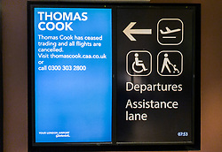 © Licensed to London News Pictures. 23/09/2019. Gatwick, UK. Passenger information screens display a message saying that 'Thomas Cook has ceased trading and all flights are cancelled' at check in desks at Gatwick Airport are closed after the travel firm collapsed overnight. The 178 year old travel operator has gone in to liquidation after rescue talks failed overnight. This will trigger the largest peacetime repatriation as more than 150,000 British holidaymakers will need to be brought home. Photo credit: Peter Macdiarmid/LNP
