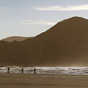 Bikers on Wharariki Beach, Golden Bay, situated just west of Cape Farewell and Farewell Spit at the northern most point of the South Island of New Zealand..Wharariki beach is approximately an hour's drive from Takaka, and is accessible by a 20 minute stroll across private, rolling farmland..The remote beach is characterised by bold cliff lines, high arches, caves, sand dunes and is home to fur-seals and seabirds. The wind sweeping the western coast has resulted in quirky, intriguing bushland. Wharariki Beach, South Island, New Zealand. 7th February 2011. Photo Tim Clayton..