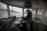 Ketchikan Gateway Borough airport ferry captain Denny Evans departs the Ketchikan terminal to cross the Tongas Narrows to the airport terminal aboard the Ken Eichner 2 on Friday afternoon during the ferry's first crossing since a mechanical failure that put it out of service on Dec. 23. The vessel was scheduled to have one of its two, 850-horsepower Cummins diesel engines replaced in February before it reached 30,000 hours of service, but because of the breakdown, the engine change was expedited, according to borough information. During the repair, additional issues were found with the driveshaft, which required a waiting period for parts to arrive. The airport ferry Oral Freeman provided service while the repairs were made. Evans, who spent about 35 years in the logging industry, began working on the Ken Eichner 2 as a deckhand about 10 years ago. After five years, he acquired a 100-ton master license from University of Alaska Southeast, and became one of three captains for the airport ferry service. Ferry crews work either the night or the day shift, but all are on call for after-hours medical evacuation service and transportation of larger loads of fuel. Staff photo by Dustin Safranek