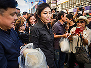 11 NOVEMBER 2016 - BANGKOK, THAILAND: YINGLUCK SHINAWATRA (center left) walks through a crowd of supporters at a rice distribution sale in the Bangkok suburbs. Yingluck Shinawatra, the former Thai Prime Minister deposed in a coup in 2014, has started selling rice directly to Thai consumers. She buys the rice from farmers at market prices and then sells it to urban consumers at the price she paid. She said she's doing it to help out farmers, who are trying to deal with depressed prices. Yingluck is facing prosecution on corruption related charges going back to a rice price support scheme her government used to try to help farmers in 2011 and 2012. Even after the coup, she is still personally popular and hundreds of people showed up to see her at the rice distribution point at a mall in Samut Prakan province, in suburban Bangkok.   PHOTO BY JACK KURTZ