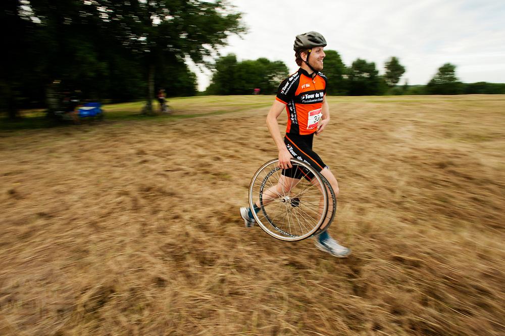 Een koerier van een bakfiets loopt met twee wielen naar een checkpoint. In Nieuwegein wordt het NK Fietskoerieren gehouden. Fietskoeriers uit Nederland strijden om de titel door op een parcours het snelst zoveel mogelijk stempels te halen en lading weg te brengen. Daarbij moeten ze een slimme route kiezen.<br /> <br /> A messenger of a cargo bike runs with two wheels to a checkpoint. In Nieuwegein bike messengers battle for the Open Dutch Bicycle Messenger Championship.
