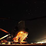 A long exposure shows the star -filled sky over soldiers waiting to be transported by chinook helicopter from Jalalabad Airfield Afghanistan.
