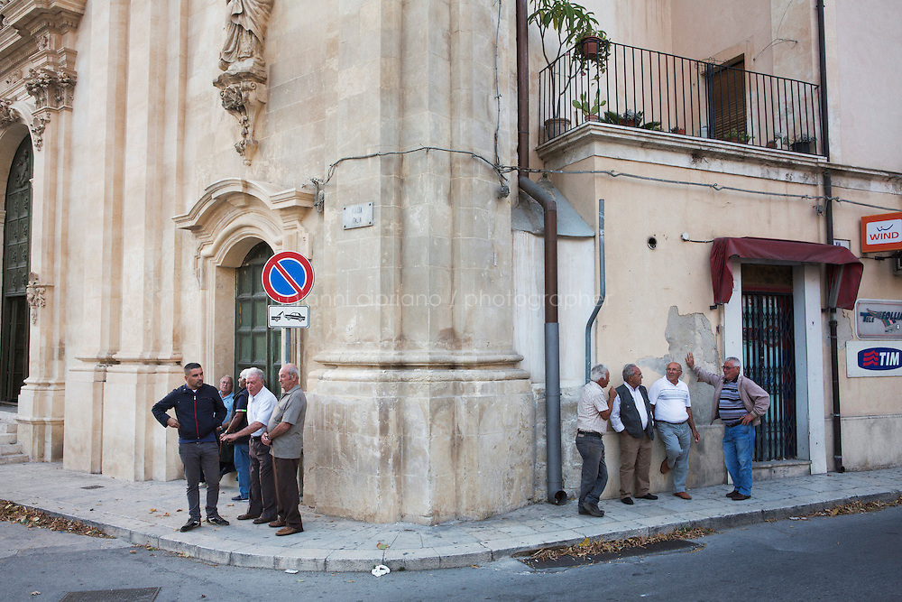 """SCICLI, ITALY - 22 OCTOBER 2014: Men chat in Piazza Italia in Scicli,  where scenes of the TV series """"Il Commissario Montalbano"""" have been shot, in Scicli, Italy, on October 22nd 2014."""