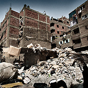 """Hombres clasificando papel en un descampado al lado de unos edificios de Mokattam . En medio del barrio de Manshiet Nasr a las afueras de El Cairo esta situado el asentamiento de Mokattam conocido como la """"Ciudad de la Basura"""" , está habitado por los Zabbaleen ,una comunidad de unos 45.000 cristianos coptos que viven desde hace varias décadas de reciclar los desperdicios que genera la capital egipcia: plástico, aluminio, papel y desechos órganicos que transforman en compost . La mayoría forman parte de la Asociación para la Protección del Ambiente (APE) una ONG que actúa en el área, cuyos objetivos son proteger el medio ambiente y aumentar el sustento de las recuperadores de basura de El Cairo. Según la ONU, el trabajo que se realiza en Mokattam como uno de los diez mejores ejemplos del mundo en el mejoramiento medioambiental. El Cairo , Egipto, Junio 2011. ( Foto : Jordi Camí )"""