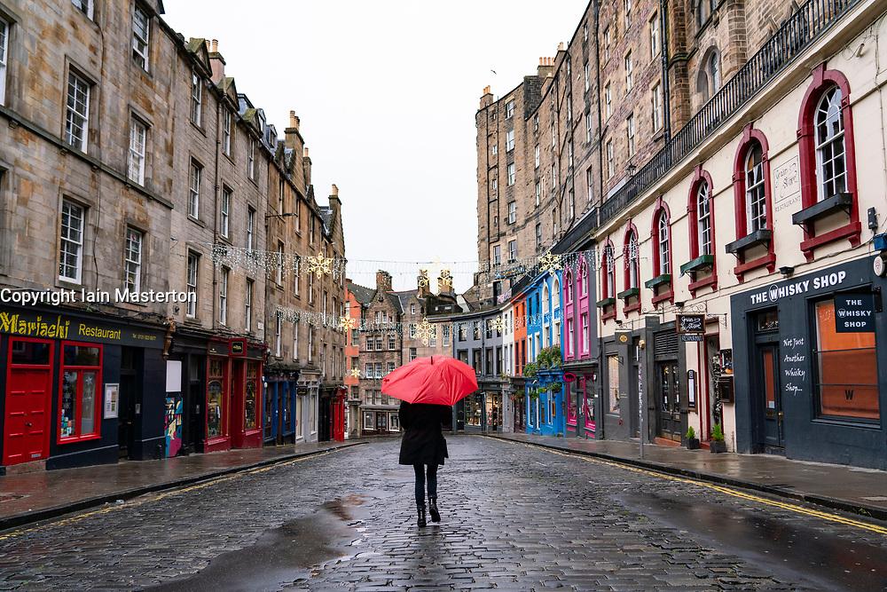 Woman holding red umbrella in rain in Victoria Street in Old Town of Edinburgh, Scotland, UK
