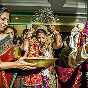 As the bride steps out of the house, she throws back five handfuls of rice over her head, in a way that it falls on the person standing behind her. This is a symbol of prosperity and wealth. The custom signifies that the bride is paying back all that her parents have given her in all these years of her stay with them. The rice also symbolizes prosperity and her wish that the house she is leaving behind should always flourish. Delhi, 2008