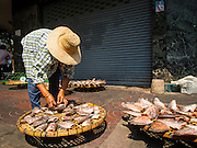 03 FEBRUARY 2015 - BANGKOK, THAILAND: A fish monger sets up her sun dried fish for sale on a sidewalk on Chareon Krung Road in the Chinatown section of Bangkok. After months of relative calm following the May 2014 coup, tensions are increasing in Bangkok. The military backed junta has threatened to crack down on anyone who opposes the government. Relations with the United States have deteriorated after Daniel Russel, the US Assistant Secretary of State for Asian and Pacific Affairs, said that normalization of relations between Thailand and the US would depend on the restoration of a credible democratically elected government in Thailand.    PHOTO BY JACK KURTZ