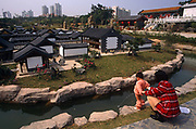 With few visitors to see, a young boy pees into the water surrounding a model town at the Splendid China model village, the 30 hectares large tourist attraction in the city of Shenzen, China. The kid aims into the water with his mother's help. In the background we see some of the 50,000 ceramic figures and scenes from a period in Chinese history and further away, modern skyscrapers in the metropolis contrasting with ancient, traditional village life. Splendid China is an attraction at the Overseas Chinese Town, Shenzhen that has scaled down replicas of China's historical buildings, wonderful scenes and folk customs. The scale models are of a 1:15 with 100 miniaturized landmarks such as The Terracotta Warriors; Great Wall; Forbidden City; Old Summer Palace etc. all laid out according to their geographic locations.