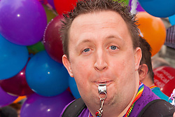 London, June 28th 2014. A man blows his whistle as the Pride London parade proceeds through the city's streets.