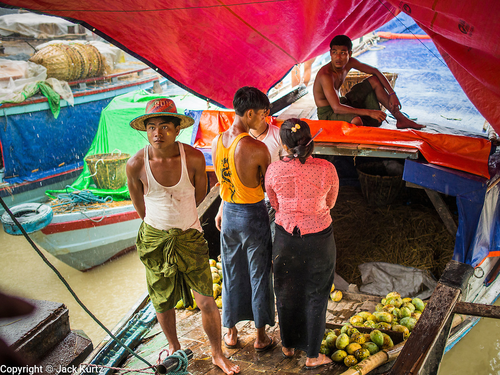 """10 JUNE 2014 - YANGON, MYANMAR:   Men on a mango boat wait out a monsoon storm on the banana jetty. The """"banana jetty"""" is on the Yangon River north of central Yangon on Strand Road. Bananas, coconuts and other fruit are brought in here from upcountry, sold and reshipped to other parts of Myanmar (Burma). All of the labor here is done by hand. Porters carry the produce to the jetty and porters load the boats before they steam upriver.   PHOTO BY JACK KURTZ"""