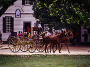 Visitors and school group watching horses with wagon at Colonial Williamsburg, the restored eighteenth-century capital of Virginia.