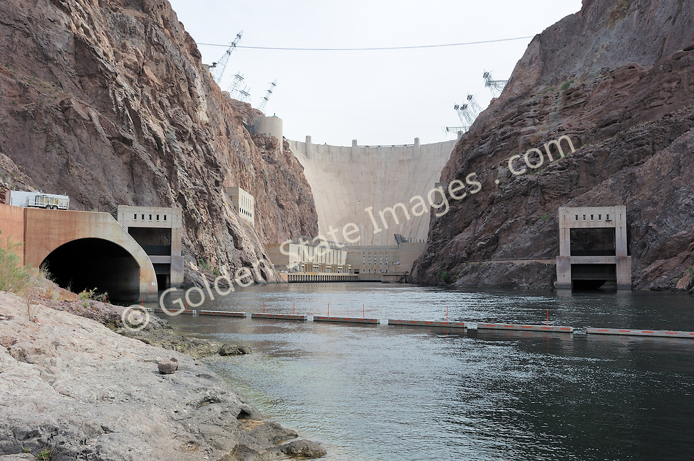 The base of Hoover Dam from Black Canyon.<br /> <br /> Hoover Dam is designed to never have the water level of Lake Mead overtop the dam. There are spillways on each side which route excess storage around the dam.