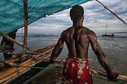 Antandroy fishermen pulling pirogue out to sea at pre-dawn. The narrow wooden canoes with their one stabalizer are remarkably sea worthy. The sail is made from cotton or woven plasitc sacking. Lavanono fishing village, south coast of MADAGASCAR