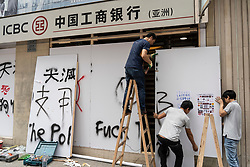 Kowloon, Hong Kong, China,. 7 October, 2019. After a night of violent confrontations between police and pro-democracy protestors in MongKok and YauMaTei in Kowloon, many MTR railway stations and what are thought to be pro-Beijing business franchises were vandalised. Workers fitting hoardings to protect Chinese ICBC Bank