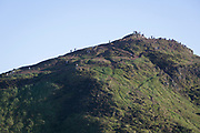 "In summer evening sunshine, walkers climb the last metres to the summit of Arthur's Seat in Holyrood Park that overlooks the city of Edinburgh, on 26th June 2019, in Edinburgh, Scotland. Arthur's Seat is an extinct volcano which is considered the main peak of the group of hills in Edinburgh, Scotland, which form most of Holyrood Park, described by Robert Louis Stevenson as ""a hill for magnitude, a mountain in virtue of its bold design"". The hill rises above the city to a height of 250.5 m (822 ft), providing excellent panoramic views of the city and beyond."