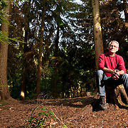A healthy lifestyle campaign of a senior gentleman, alone whilst walking in woodland.