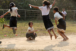 Groups of girls take part in jumping and skipping games during their break time. Vang Mak primary school, Vieng thong district, Bolikhamxai Province, Lao PDR