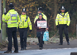 © Licensed to London News Pictures. 04/12/2019. Watford, UK. Lone protestor Stuart Holmes is escorted by police at the gates to The Grove Hotel where NATO leaders are meeting. World leaders are attending a series of events over the two day NATO summit which will mark the 70th anniversary of the alliance of nations. Photo credit: Peter Macdiarmid/LNP