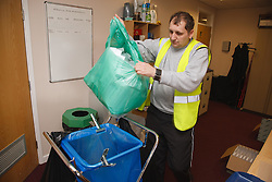 Man with a mild learning disability working as a factory cleaner, shown here recycling paper, helped into employment by the Ready 4 Work team, Nottinghamshire County Council