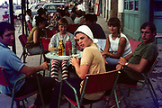 Group of young British people on holiday sitting around a cafe table, Spain, 1966
