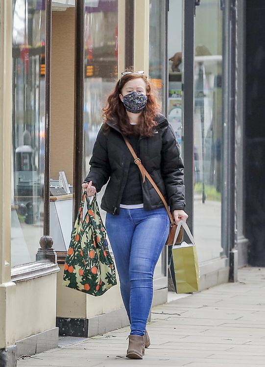 12th, March, 2021. Cheltenham, England. A shopper walks through the town centre wearing a mask.