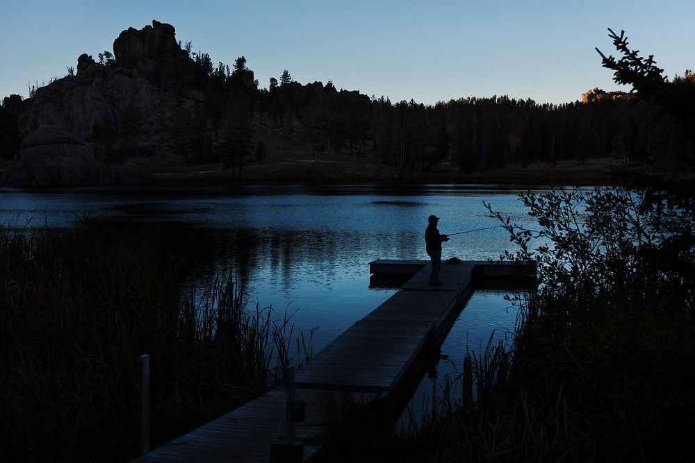 A man fishes at twilight at Sylvan Lake near the Needles Highway in The Black Hills region