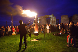 © licensed to London News Pictures. Wiltshire, UK 10/07/2012. People watching a fire post at Stonehenge as they enjoy Fire Garden event which is part of the London 2012 Festival and Salisbury International Arts Festival. The heritage site surrounded with fire sculptures and fire posts by French outdoor fire alchemists Compagnie Carabosee. Photo credit: Tolga Akmen/LNP