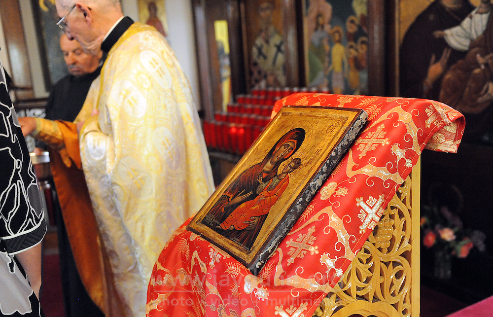 A handpainted icon is front and center for Sunday's service at St. John the Baptist Greek Orthodox Church in Salinas. Father Mark Vinas, left, blesses parishioners as they leave.