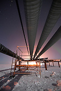 Alaska, North Slope. A recently completed scaffold sits under the pipeline with a faint glimmer of northern lights in the sky.