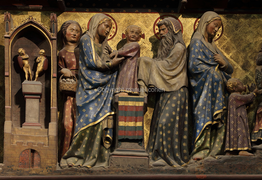 Presentation in the temple, painted carved section of the North choir screen, between the ambulatory and the sanctuary, carved 1300-50, by Pierre de Chelle, Jean Ravy and Jean Le Bouteiller, in the Cathedrale Notre-Dame de Paris, or Notre-Dame cathedral, built 1163-1345 in French Gothic style, on the Ile de la Cite in the 4th arrondissement of Paris, France. The infant Jesus is presented by Joseph and Mary, with Anna on the left. To the left, idols fall away, and to the right, the infant Jesus with the doctors of the law. Picture by Manuel Cohen