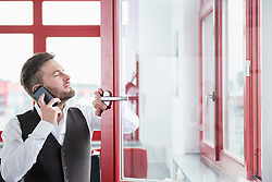 Young man office open window using Smartphone