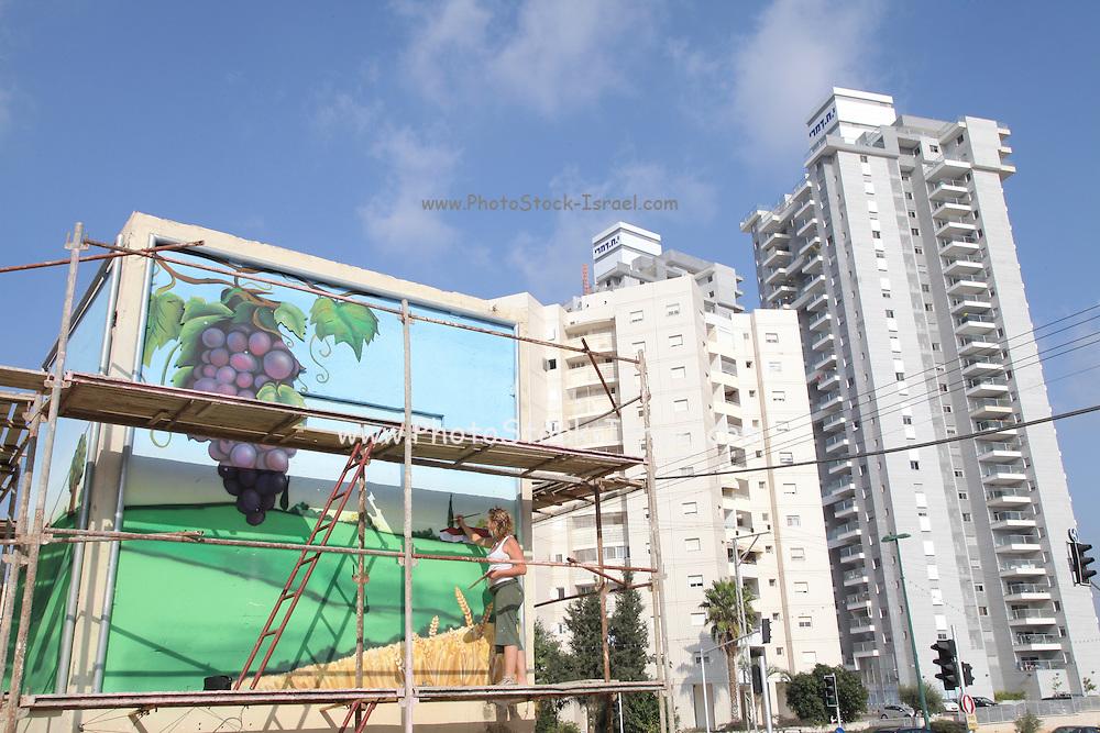 Painter paints a mural in Natanya, Israel