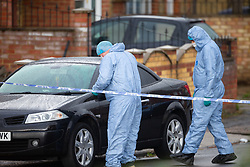 Forensics investigators examine a car parked near a VW Polo with its windows smashed and a Vauxhall Zfafira with damage to its front left corner,  thought by police to be connected to Sunday evening's quadruple stabbing on Fraser Road, Edmonton in North London and possibly to be linked to a shooting on Gordon Road on Saturday 17th November. Edmonton, London, November 19 2018.