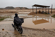 A man protects himself from the rain in Huepetuhe, Peru. Huepetuhe is a town where the largest gold extraction is concentrated and where people work every day, destroying the Amazon rainforest.