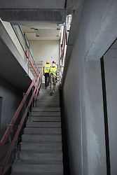 Construction workers walking upstairs at building site, Munich, Bavaria, Germany