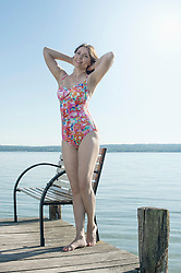 Mature woman standing in swimsuit on pier and smiling, Bavaria, Germany