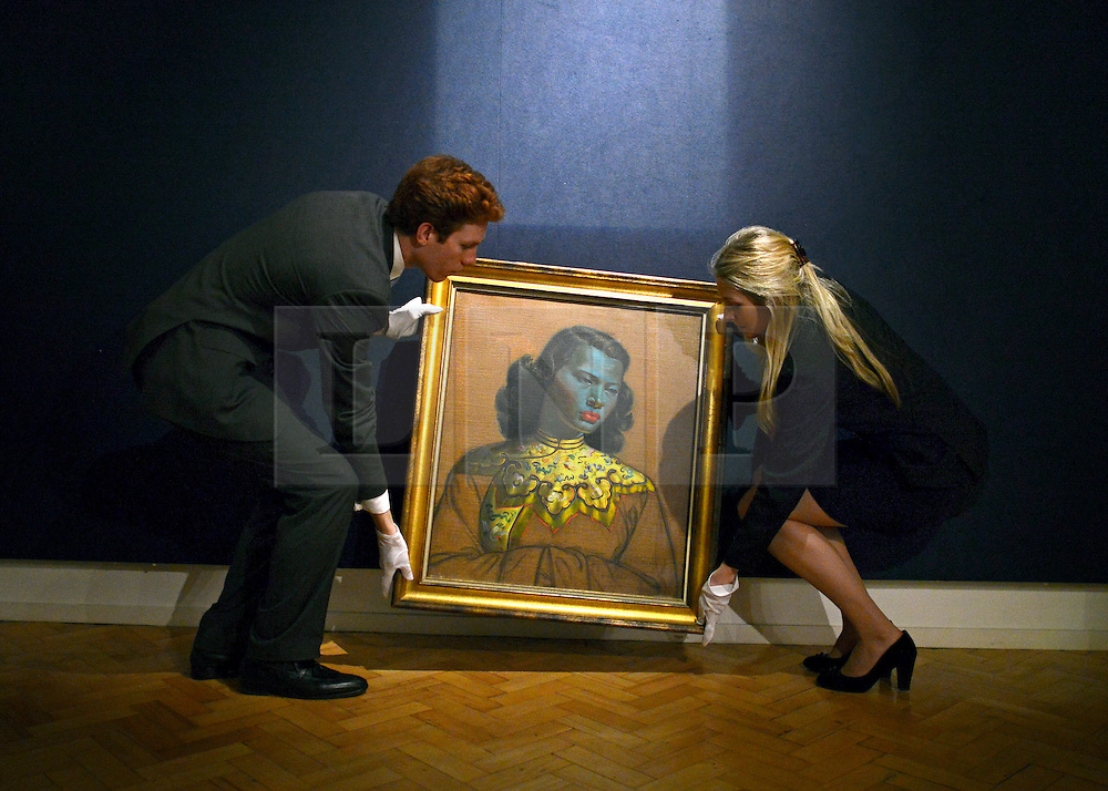 """© Licensed to London News Pictures. 18/03/2013. London, UK A gallery staff hang the painting. Press call before the auction of """"Chinese Girl"""" by Vladimir Tretchikoff at Bonhams in London today 18th March 2013. The painting is said to be the most widely reproduced and recognisable painting in the world because of its wide reproduction in 1950's art prints. It is expected to fetch 300,000-500,000 GBP at auction on the 20th March. Photo credit : Stephen Simpson/LNP"""
