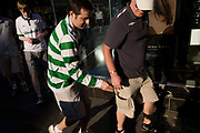 Football supporter mates mess around in a London street before going on to watch their team's match elsewhere in the capital. But this man in the green stripes of his team is NOT a pickpocket as might be suggested on first look. He reaches into the unbuttoned pocket of the older-looking man in shorts. But recaptioning this picture to suggest he is a street criminal might be thought libellous, giving this brief moment a misinterpretation and misrepresentation.
