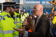 Environmental activists argue with police officers while protesting about Climate Change during the occupation of City Airport Londons Business Travel hub in east London, the fourth day of a two-week prolonged worldwide protest by members of Extinction Rebellion, on 10th October 2019, in London, England.