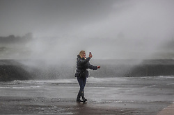 © Licensed to London News Pictures. 09/02/2020. Portsmouth, UK. A woman defies the waves to take a selfie at high tide on the sea front at Southsea, Portsmouth as Storm Ciara batters the UK. Airlines have cancelled dozens of domestic and international flights as the storm brings strong winds and rain. Photo credit: Peter Macdiarmid/LNP