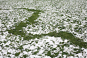 A zig-zag trail of bare grass is left by snowman-builders in fast-disappearing snow after winter snows brought seasonal disruption to London, but a welcome playground for those on school-free days.