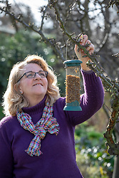 Hanging up a bird feeder filled with mealworms