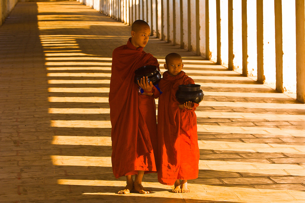 Two monks walking down hallway at the Shwezigon Pagoda, Bagan, Myanmar (Burma)