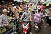 14 MARCH 2006 - PHNOM PENH, CAMBODIA: People drive through the main maket in Phnom Penh, Cambodia.Many people in Cambodia don't have refrigerators and shop for meat and produce almost every day.   PHOTO BY JACK KURTZ