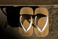 Geta are a form of traditional Japanese footwear that resembles both clogs and flip-flops. They are a kind of sandal with an elevated wooden base held onto the foot with a fabric thong to keep the foot well above the ground. They are worn with traditional Japanese clothing such as kimono or yukata, and even with Western clothing during the summer months. Geta are often worn in rain or snow to keep the feet dry, due to their extra height.