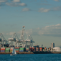 A sailboat floats past giant containers being unloaded from ships at Long Beach Harbor, California.