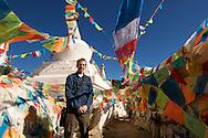A tourist poses amoung Tibetan Buddhist prayer flags near Deqin, Tibet (China).