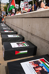 """London, August 23rd, 2014. """"Coffins"""" line the pavement, each one bearing a picture of children killed since Israel began its Operation Protective Edge against Hamas as hundreds of pro- Palestine protesters demonstrate outside Downing Street demanding that Britain stops arming Israel."""